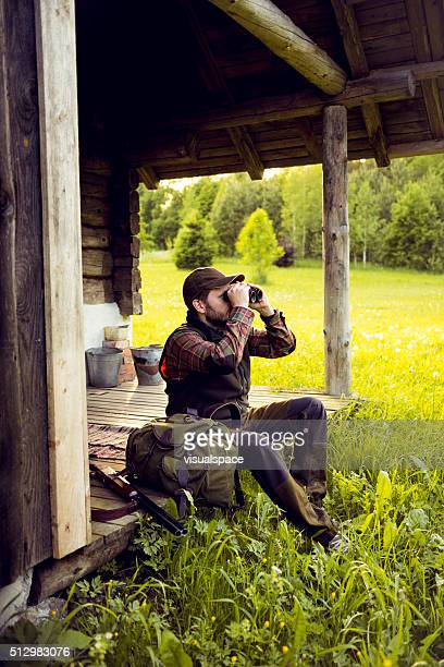 Man On His Wooden House Terrace Ready To Go Hunting