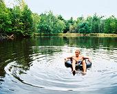 Man on inner tube in pond