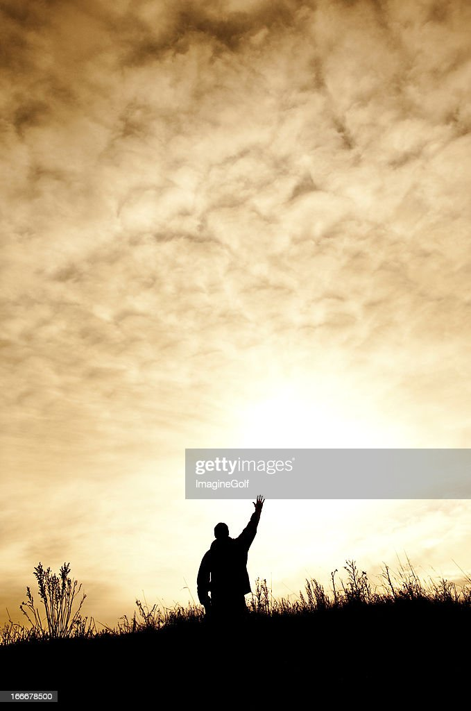 Man On Knees in Praise and Worship Silhouette