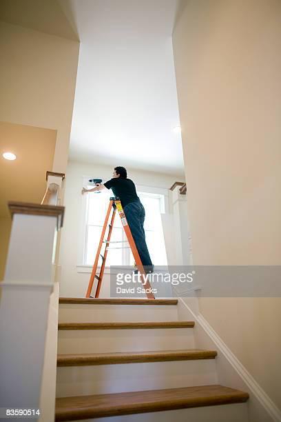 Homme sur échelle, fixation fenêtres de la maison