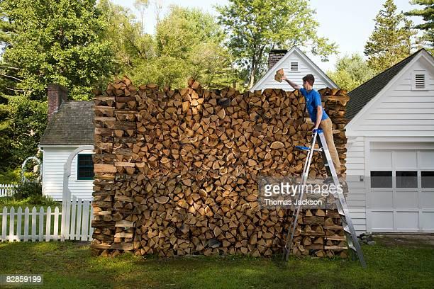 Man on ladder, stacking wood