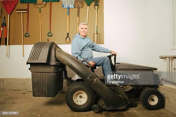 Man on lawn mower in garage, portrait