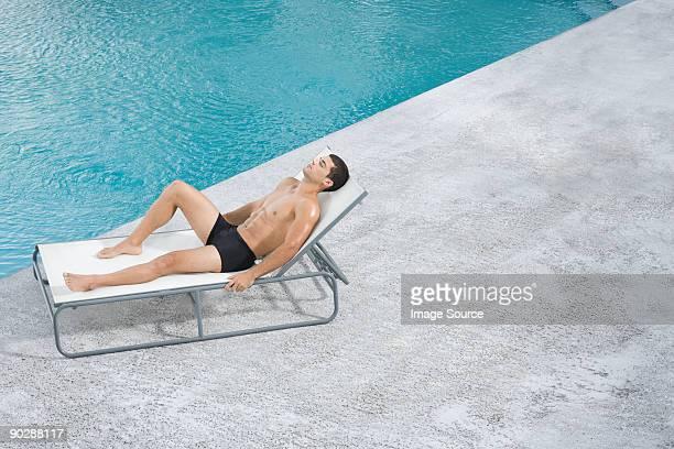Homme sur une chaise longue au bord de la piscine