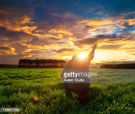 Man on meadow praying to god facing the sun