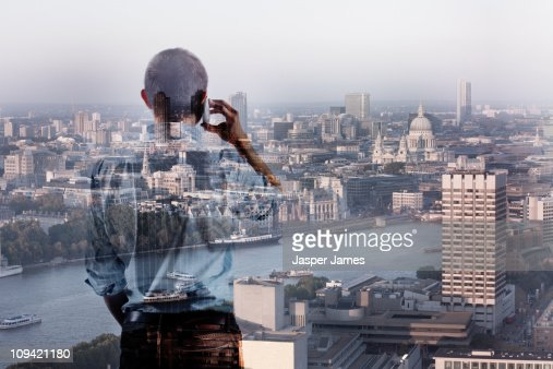 Man on mobile phone in front of London cityscape,d : Stock Photo