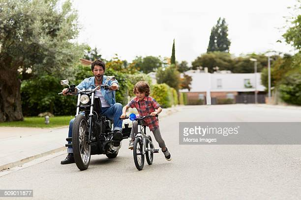 Man on motorbike chasing son riding bicycle