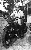 Happy Man on motorbike in 1945. He is stationary in an urban road. Some skratches and grain due to the age of the photo. Scanned black and white print.