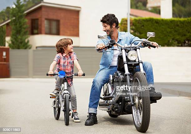 Man on motorbike looking at son riding bicycle