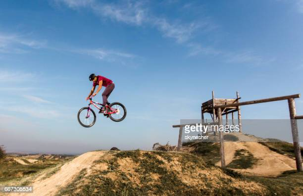 Man on mountain bike straight air jumping against the sky.