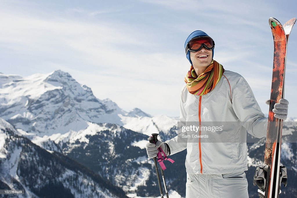 Man on mountain holding skis