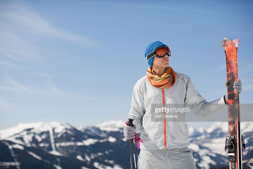 Man on mountain holding skis : Stock Photo
