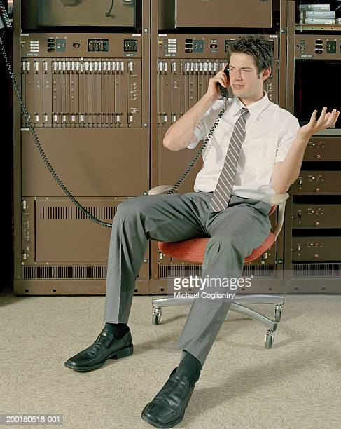 Man on office chair using telephone by network servers