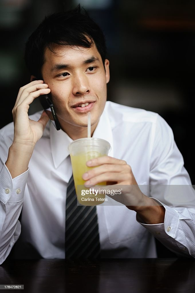 Man on on the phone drinks juice : Stock Photo