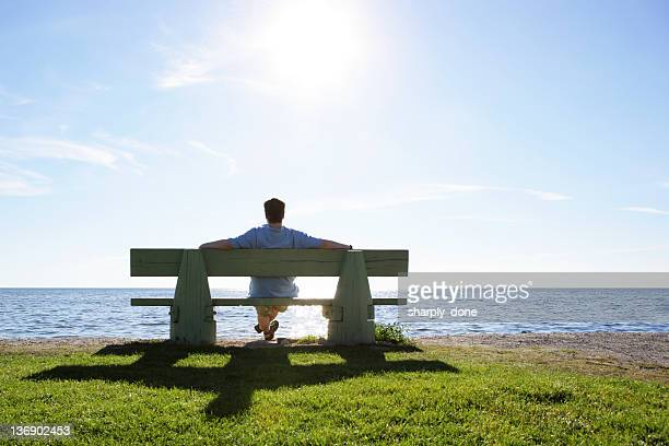 XL hombre en banco del parque con vista al mar