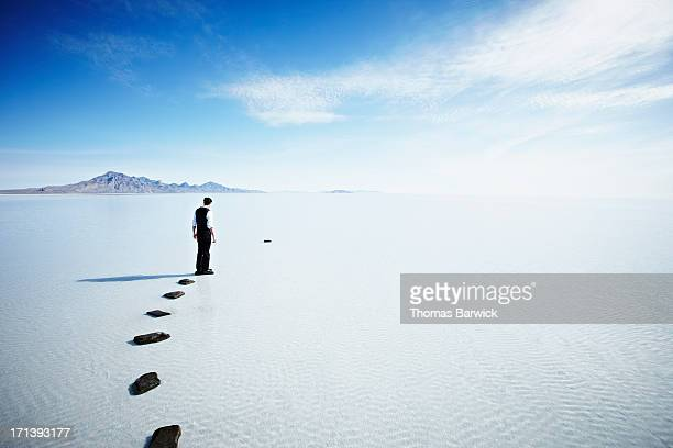 Man on path in lake looking at gap in stones