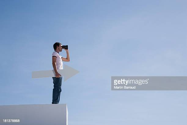 Man on pedestal with binoculars and arrow