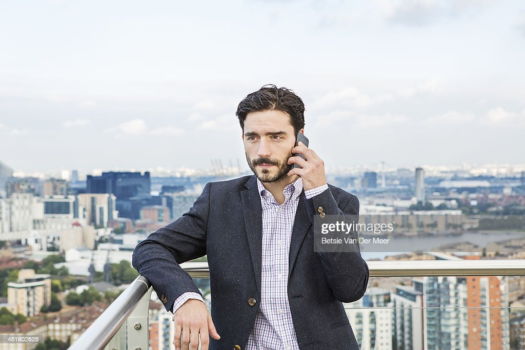 Man on phone on balcony overlooking city. : Stock Photo