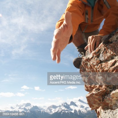 Man on precipice extending hand in help, low angle view : Stock Photo