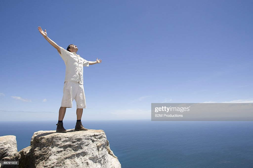 Man on rock arms up : Stock Photo