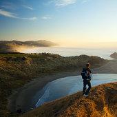 Man on rocky coast, morning light
