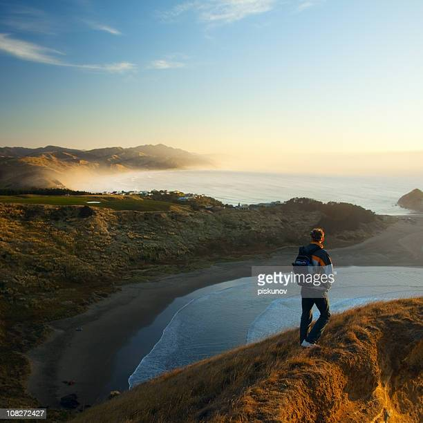 Man on rocky coast, morning light