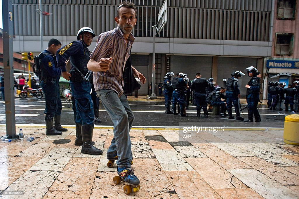 A man on roller skates passes in front of policemen during a protest of students and teachers in demand of a higher budget for educaction in Caracas on May 27, 2010. AFP PHOTO / Miguel GUTIERREZ