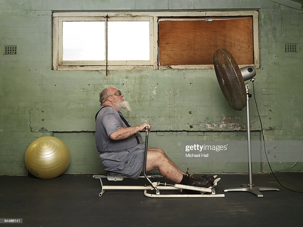 Man on rowing machine : Stock Photo