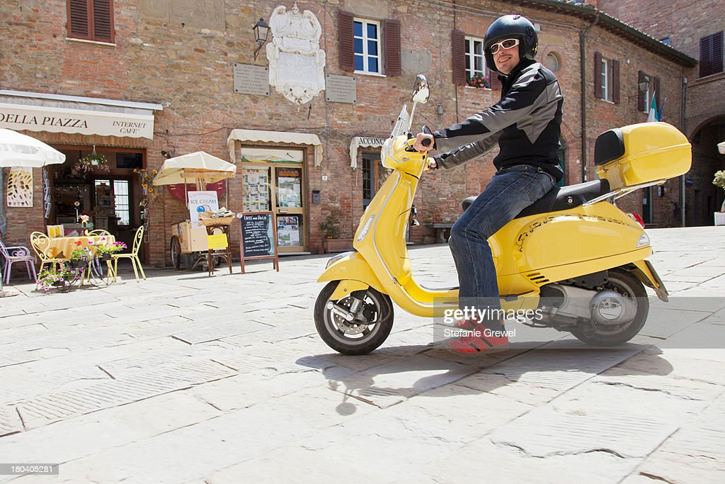 Man on scooter in village square