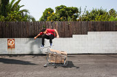 Man on skateboard jumping over a shopping trolley