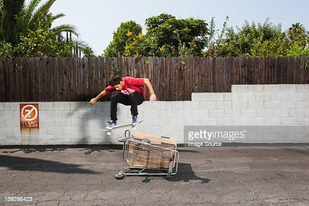 Uomo su skateboard saltare su un carrello acquisti