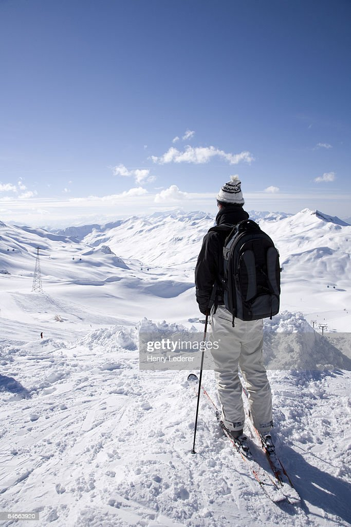 Man on skis looking over swiss alps : Stock Photo