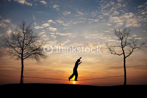 man on slackline in sunset : Stock Photo
