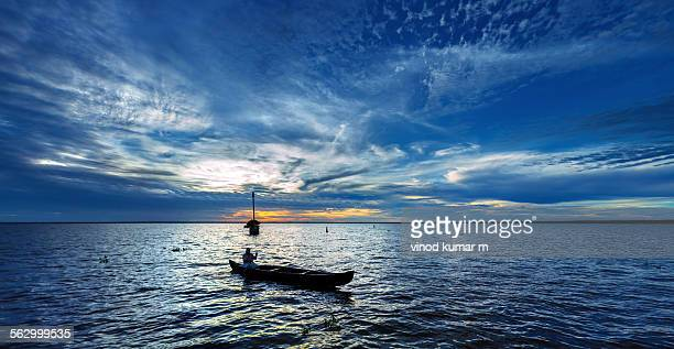Man on small boat at sunset time