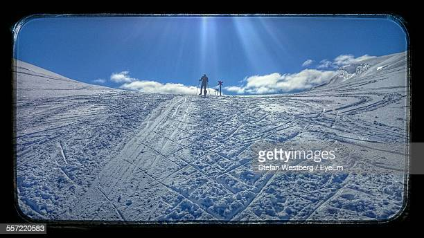 Man On Snow Covered Field Against Sky During Sunny Day