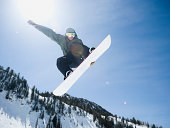 Man on snowboard in air, Wasatch Mountains, Utah, United States