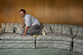 Man on sofa looking scared