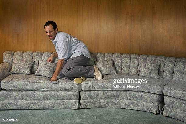 Man on sofa looking scared