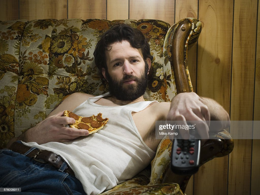 Man on sofa with pizza and remote