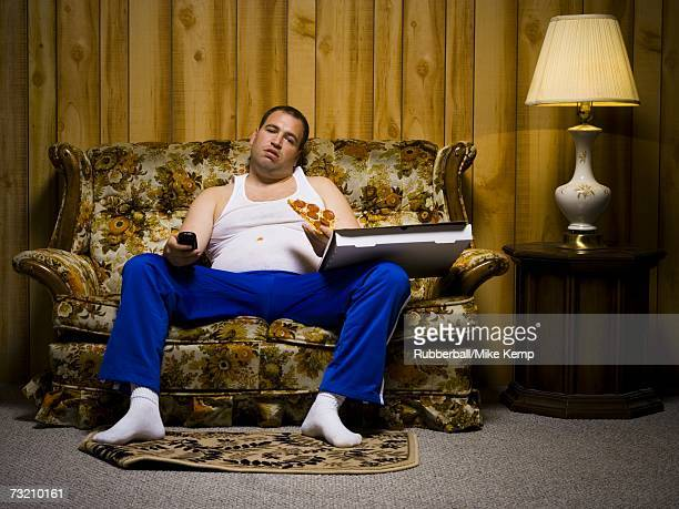 Man on sofa with pizza and TV remote