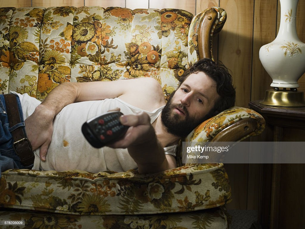 Man on sofa with television remote
