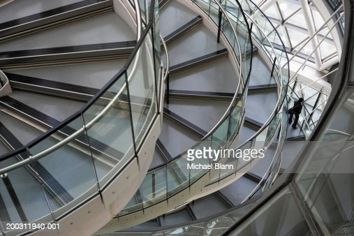 Man on spiral staircase, looking out window, elevated view : Stock-Foto