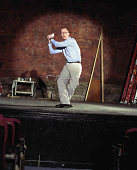 Man on stage in theater in baseball position