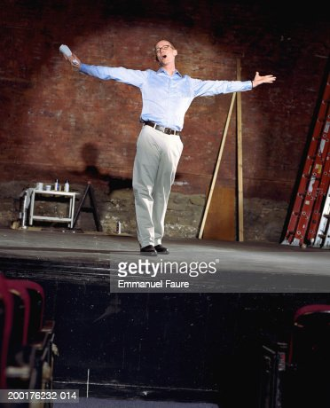 Man on stage in theater with arms outstretched