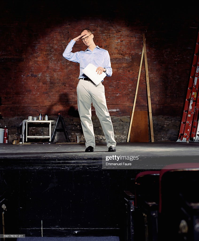 Man on stage in theater with hand on forehead