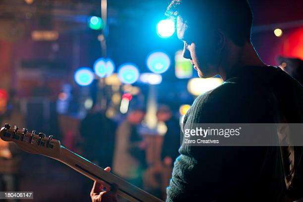 Man on stage playing guitar in nightclub