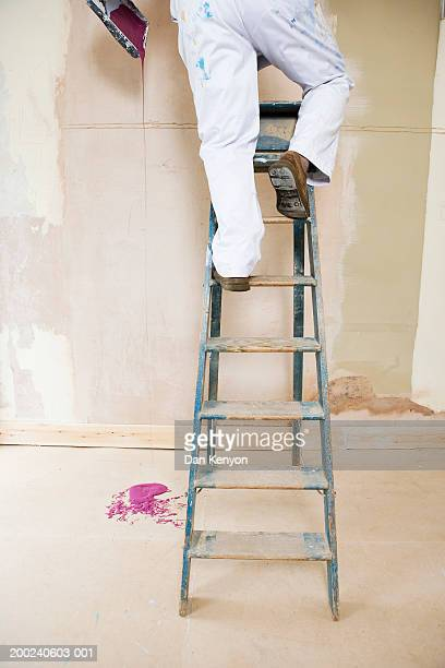 Man on stepladder holding tray dripping with paint, low section