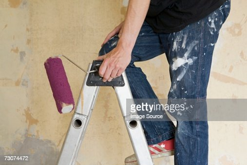 Man on stepladder with paint roller