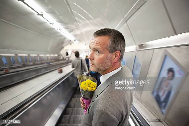 Man on subway escalator with flowers