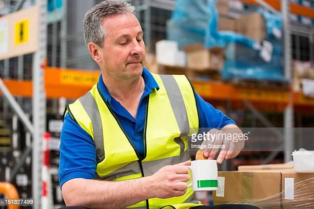 Man on tea break in warehouse