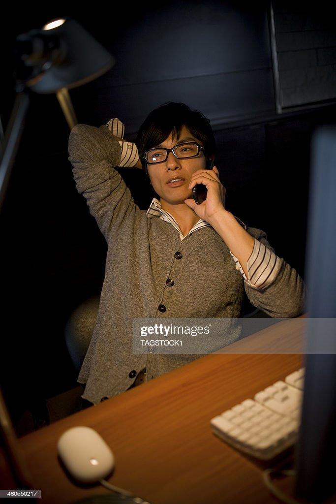Man on telephone at desk : Stock Photo